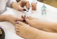 Pedikyr på skönhetsalongen Nail polering close upp royaltyfri bild