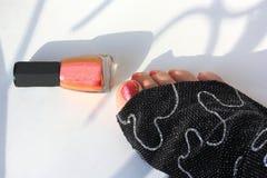 Pedikyrer och härligt spikar polermedel Den svarta torkduken och ljust rött spikar polermedel Fotografering för Bildbyråer