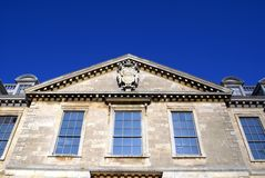 Pediment. Ornate old facade of a pediment, sculpture, cornice, and arched windows Royalty Free Stock Photos