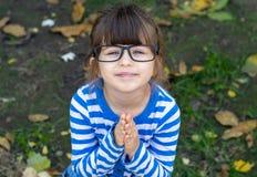 Pedir de lamentação da criança para fazer seu presente que implora guardando as mãos reza dentro os bordos de enrugamento foto de stock royalty free