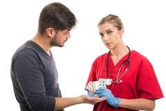 Pedir paciente masculino tabuletas ao doutor fêmea foto de stock