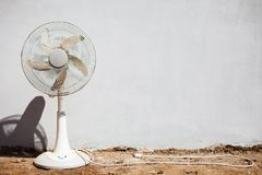 Fan and white wall. Pedistal fan placed before a white wall stock photo