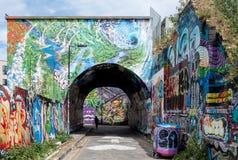 Pedley街曲拱, Shoreditch,东伦敦 在铁路线下的步行巷道在砖车道附近,盖在五颜六色的街道画 免版税库存图片