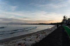 Pedone lungo la spiaggia di Kuta Bali quando la mattina è ancora calma fotografia stock
