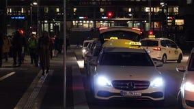 Pedoni a Amburgo alla notte con le automobili del taxi in una fila che prende i passeggeri stock footage