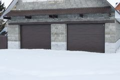 A pedra da garagem com rolo shutters na cor marrom fotografia de stock
