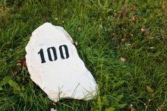 Pedra da milha na grama perto da estrada Imagem de Stock