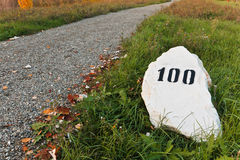 Pedra da milha na grama perto da estrada Imagem de Stock Royalty Free
