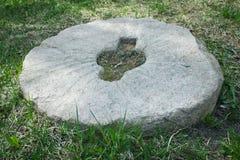 Pedra de moer de pedra velha na grama Fotografia de Stock Royalty Free