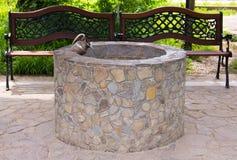 A pedra decorativa bem com a figura de um jarro está em uma alcova quieta ao lado dos bancos Imagem de Stock