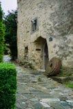 Pedra do moinho que inclina-se contra a constru??o de pedra medieval em Alemanha foto de stock royalty free