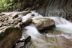 A pedra enorme que encontra-se no rio Água vibrante imagens de stock royalty free