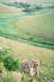 A pedra grande nas montanhas no fundo borrado dos campos e das florestas do verde Imagens de Stock Royalty Free