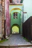 A pedra velha pavimentou a rua com os arcos da fortaleza de Sighisoara Imagens de Stock Royalty Free
