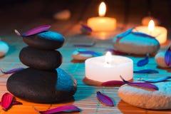 Pedras brancas e pretas, pétalas roxas, e velas Imagens de Stock Royalty Free