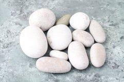 Pedras claras redondas do mar no fundo azul cinzento imagem de stock royalty free