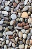 Pedras coloridas bonitas pelo mar na praia fotografia de stock