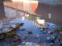 Pedras com grama e água com reflexão da construção Imagens de Stock