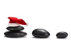 pedras com o chapéu vermelho de Papai Noel fotos de stock royalty free
