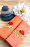 Pedras da massagem com toalhas e peony Imagem de Stock