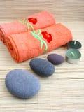 Pedras da massagem com toalhas e velas Imagem de Stock