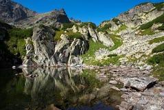 Pedras de Colorfull pelo lago da montanha Fotos de Stock Royalty Free