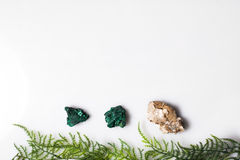 Pedras de minerais removidas em um fundo branco na parte superior com a grama verde Fotografia de Stock Royalty Free