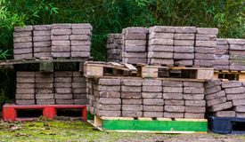 Pedras de pavimentação empilhadas em páletes, materiais de construção da rua, indústria do pavimento fotos de stock