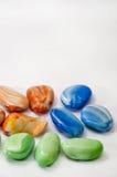 Pedras decorativas coloridas em um fundo branco Fotos de Stock
