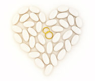 Pedras do coração embutidas com os anéis de casamento do ouro Imagens de Stock