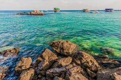 Pedras do mar e barcos de pesca que flutuam no mar Imagens de Stock Royalty Free