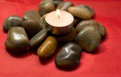 Pedras do rio, seixos e vela iluminada Fotos de Stock