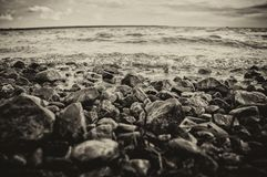 Pedras e ondas na praia da costa de mar Sepia imagens de stock royalty free