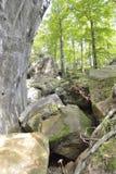 Pedras grandes sob a rocha vertical fotografia de stock