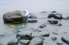 Pedras marinhas lavadas por uma onda Foto de Stock Royalty Free