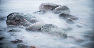 Pedras marinhas lavadas por uma onda Fotografia de Stock Royalty Free