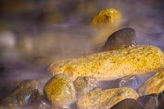 Pedras no litoral macio sonhador ondulado Imagem de Stock