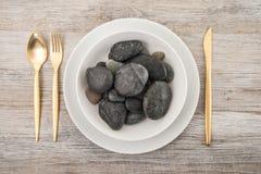 Pedras no prato no fundo de madeira Imagens de Stock