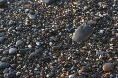Pedras pequenas do mar no brilho do fundo da textura dos seixos da praia no fundo do sol foto de stock