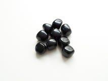 Pedras pretas caídas da obsidiana perto acima na tabela para o ther de cristal imagens de stock