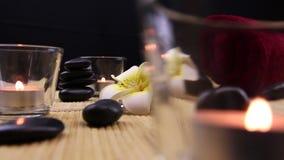 Pedras pretas da terapia dos termas cercadas por velas