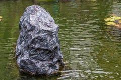 Pedras pretas grandes no fundo do jardim da água foto de stock