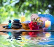 Pedras, toalha de sal do óleo da camélia da vela na água Imagem de Stock