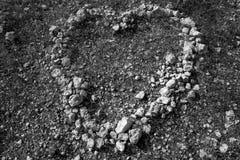 Pedras preto e branco da forma do coração no solo Fotografia de Stock Royalty Free