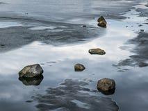 Pedras que encontram-se no gelo de derretimento de um rio congelado Fotografia de Stock
