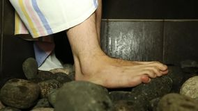 Pedras quentes na sauna e uma cubeta dos pés dos homens do close-up da água vídeos de arquivo