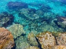 Pedras sob a beleza clara da água foto de stock