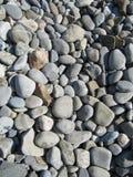 Pedras transformadas em seixos com a ajuda do mar foto de stock