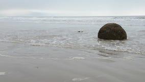 Pedregulhos de Moeraki nas ondas de Oceano Pacífico vídeos de arquivo