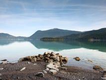 Pedregulhos grandes que colam para fora do nível de água liso do lago Água azul verde Imagem de Stock
